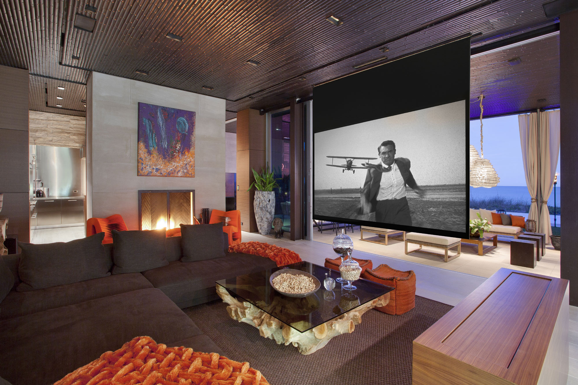 This media room at an oceanfront retreat in Vero Beach, Florida, features a fireplace; drop-down, large-format screen; and full wet bar with backlit onyx surround.