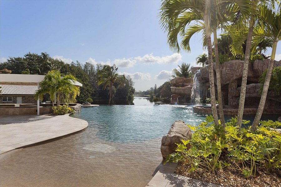 This lakeside home boasts a private water park complete with a pool, waterfall, boathouse, island, lazy river, and an underwater wall for viewing saltwater fish.
