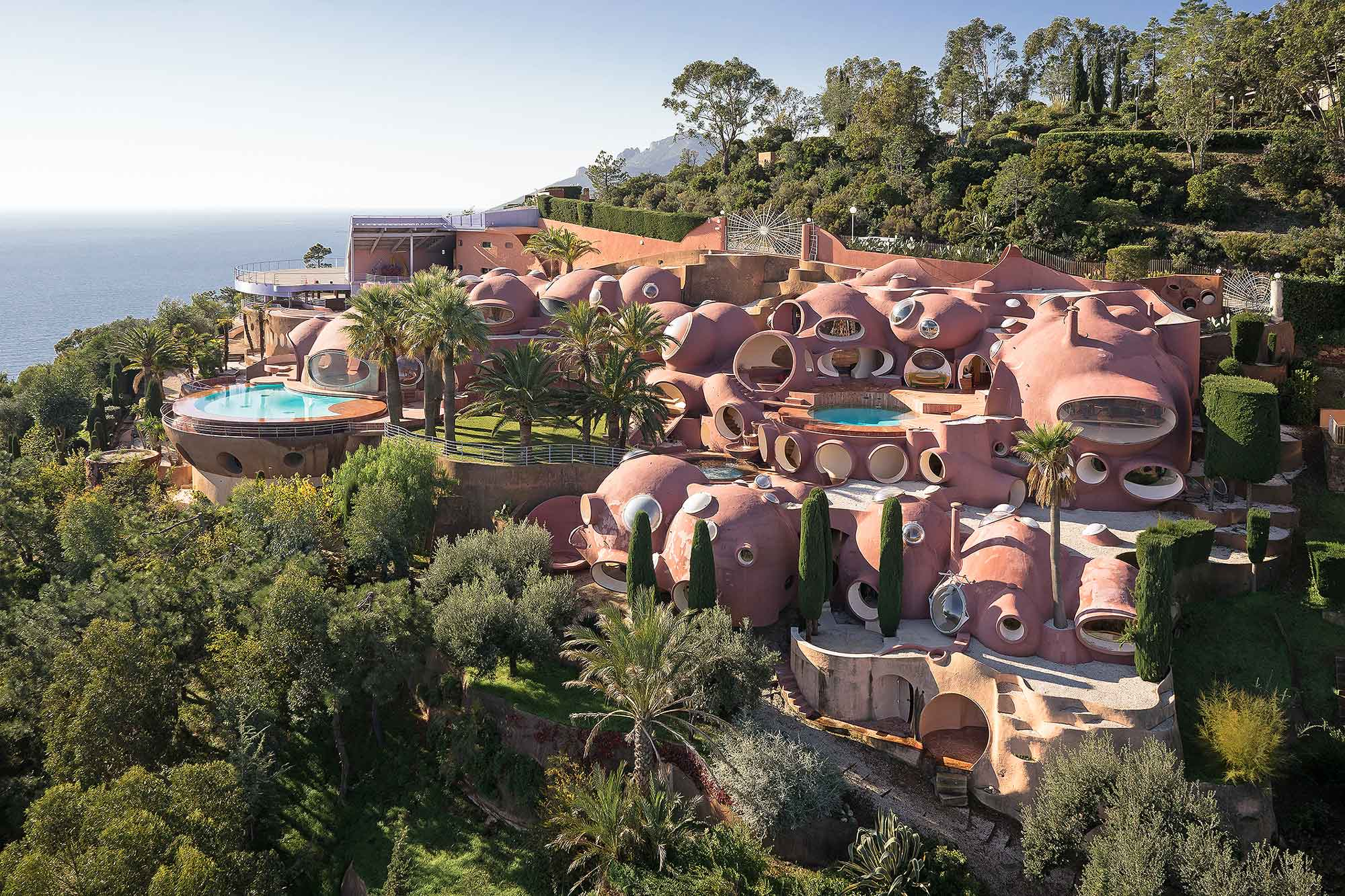 Pierre Cardin's iconic Bubble Palace was designed by Hungarian architect Antti Lovag. The unique living spaces are composed of interconnecting terracotta orbs which flow into beautiful gardens overlooking the Bay of Cannes.