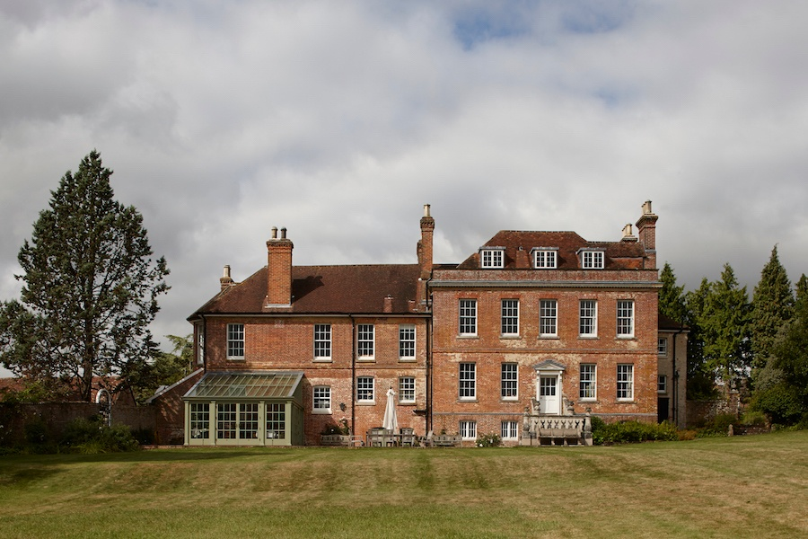 The double-fronted symmetry of this Grade II-listed brick home with its classical pediment-topped doorway and large, balanced grid windows handsomely demonstrates its Georgian origin.