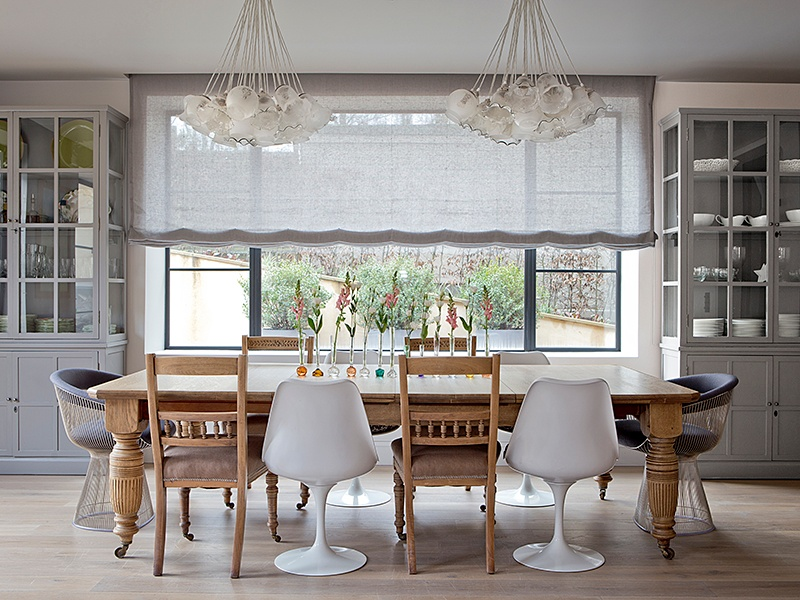 This dining room, in a newly constructed family house in Wimbledon, London, was designed by Godrich Interiors with a focus on symmetry. The bespoke chandeliers were crafted from around 80 antique glass shades, and although designers used a mix of chairs around the table, they are paired.