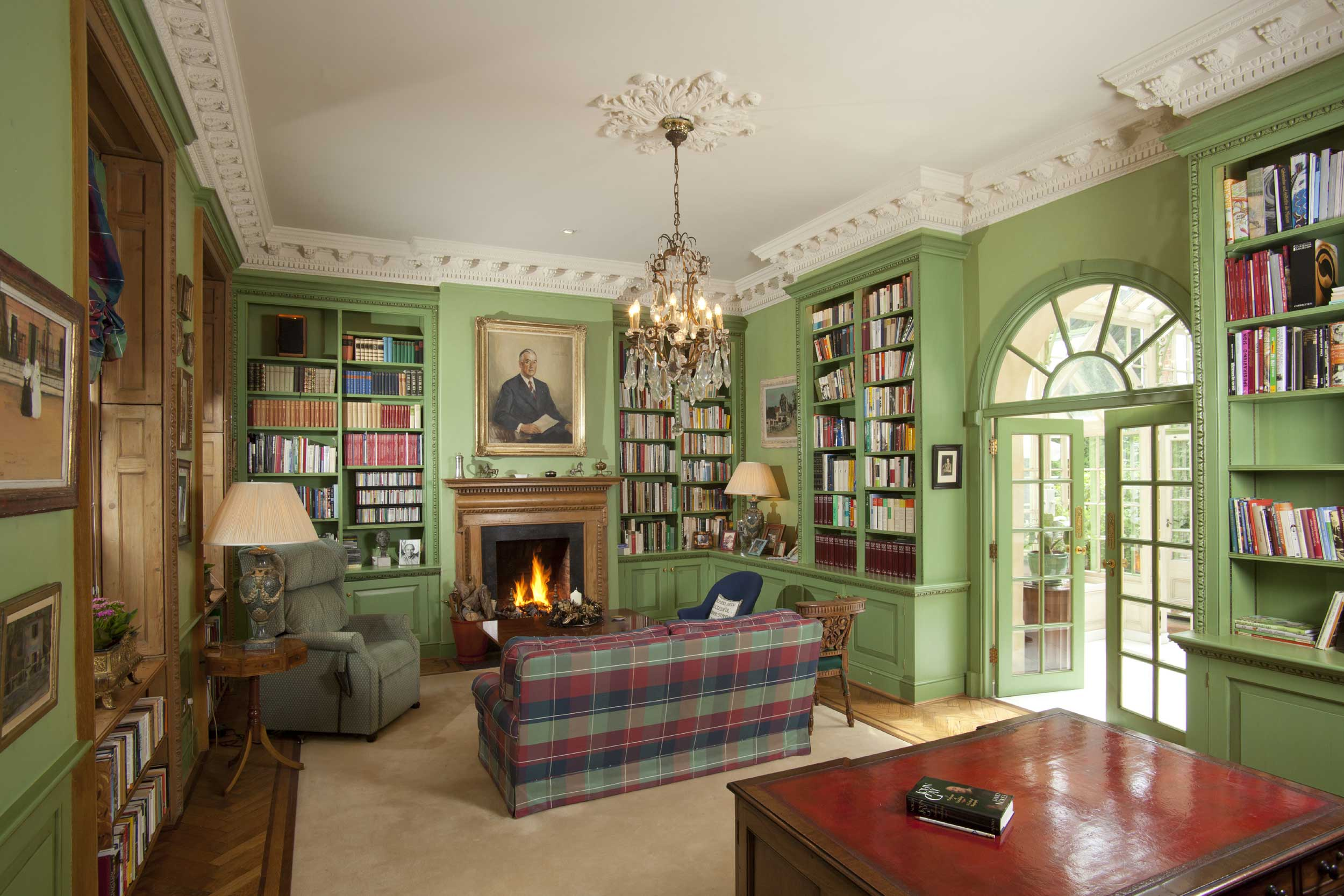 This grand residence features magnificent period details including this library accoutered in an elegant shade of green.