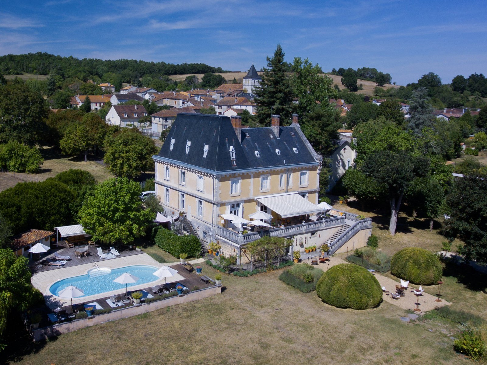 The property comprises a fine 19th-century château with two additional residences and a pool terrace in its three-hectare grounds (7.4 acres), and a third residence near the center of the village.