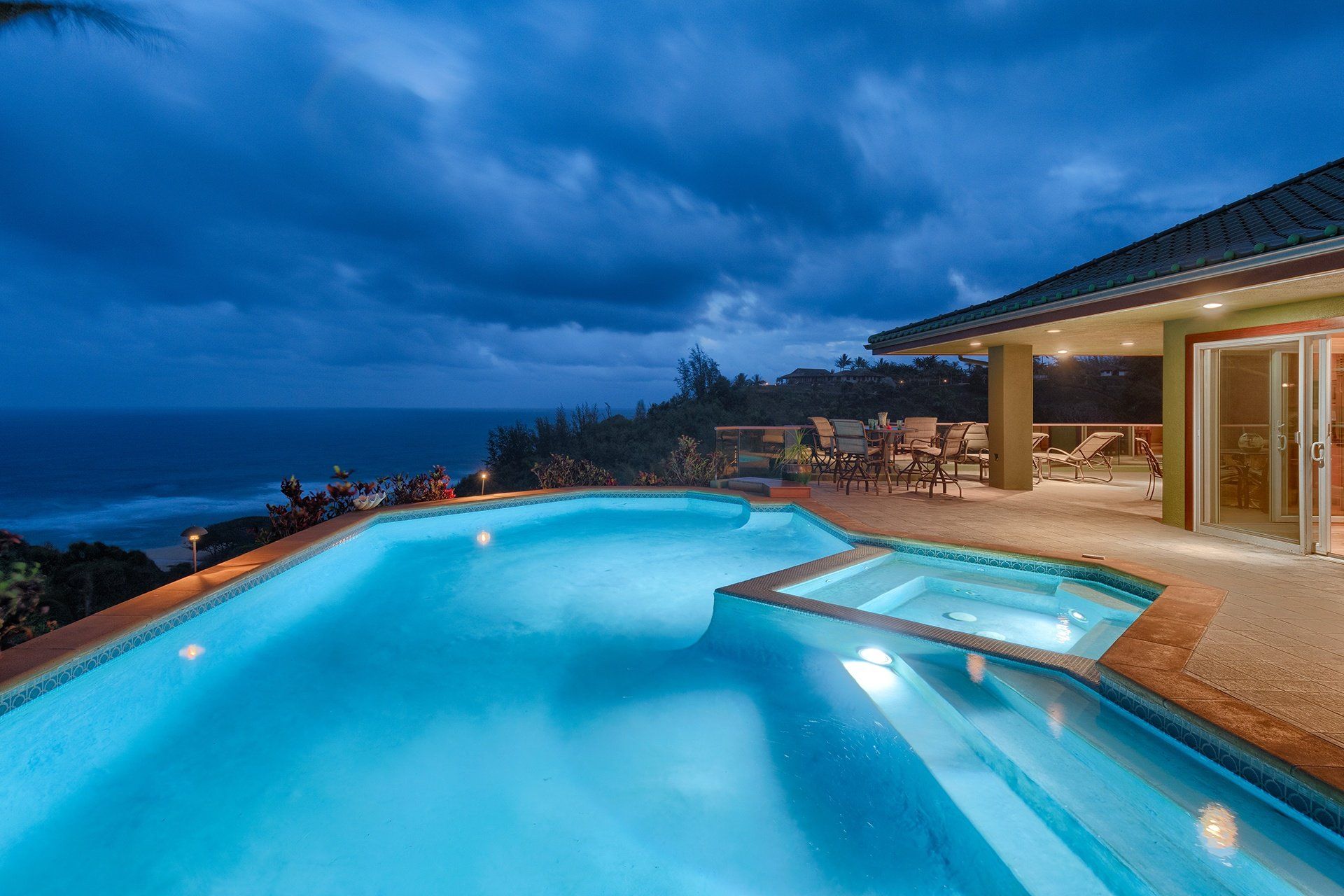 A dazzling swimming pool seems almost cantilevered over the blue Pacific beyond.