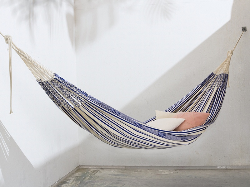 MAKA wall-mounted Poncho hammock, in blue, also available in red and green. It is made by hand by combining two Colombian artisanal weaving traditions, and is finished with a crocheted edge.
