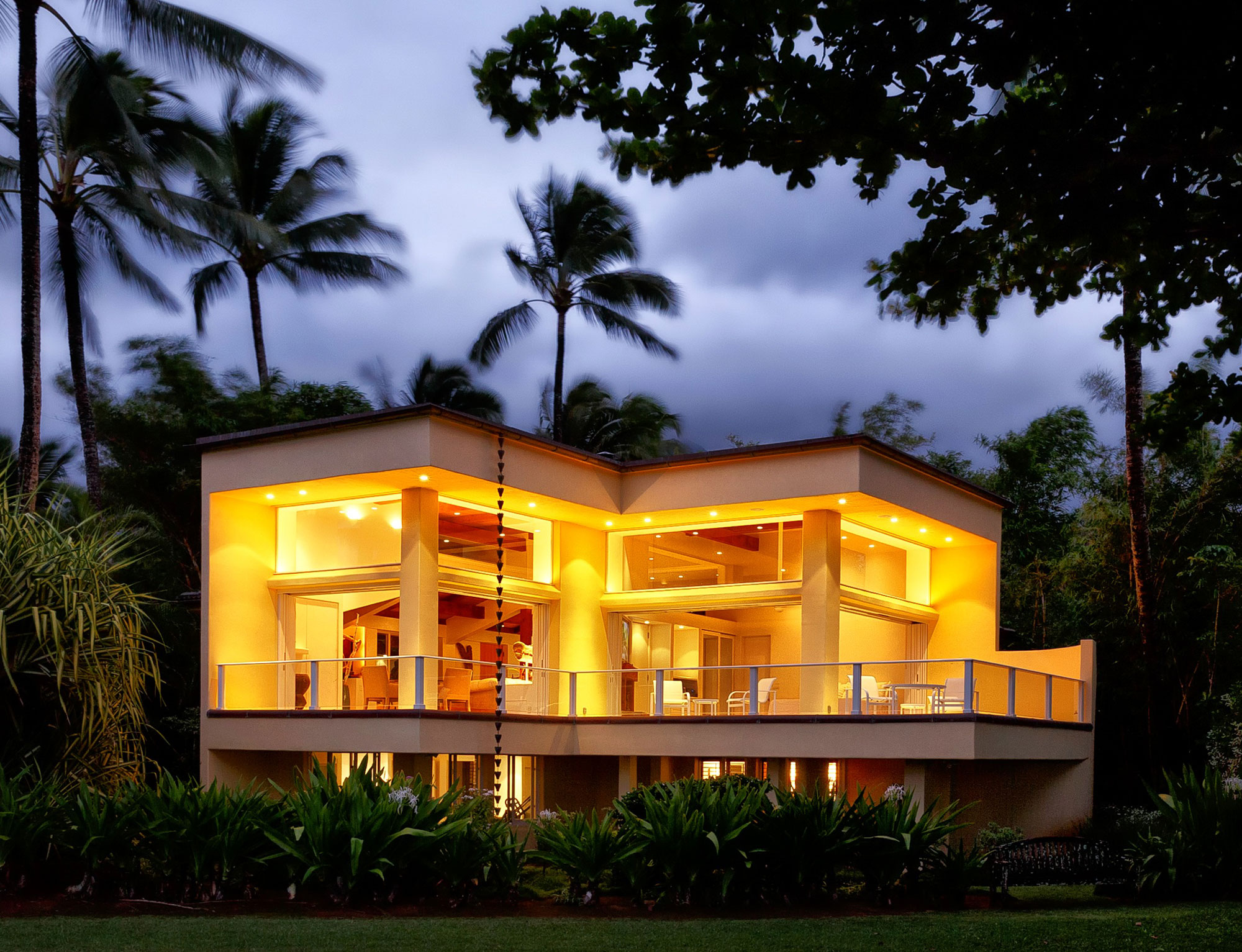 The main house, designed by famed architect James A. Schmidt, features 15-foot-high ceilings and glass pocket doors, which frame 180-degree views of Hanalei Bay.