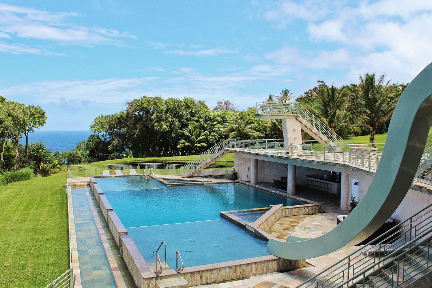 The aptly named Waterfalling Estate is an aquatic paradise featuring a 25-meter pool with a high diving platform, springboard, and waterslide.