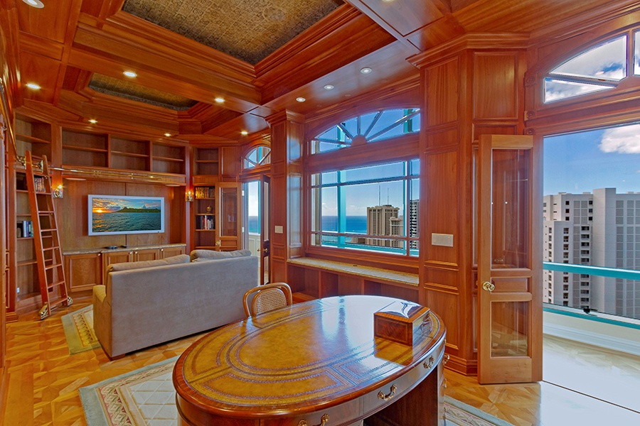 A wall-length view of Waikiki and the Pacific Ocean, as well as a private balcony for enjoying the ocean breeze, make this home's library a welcome escape.