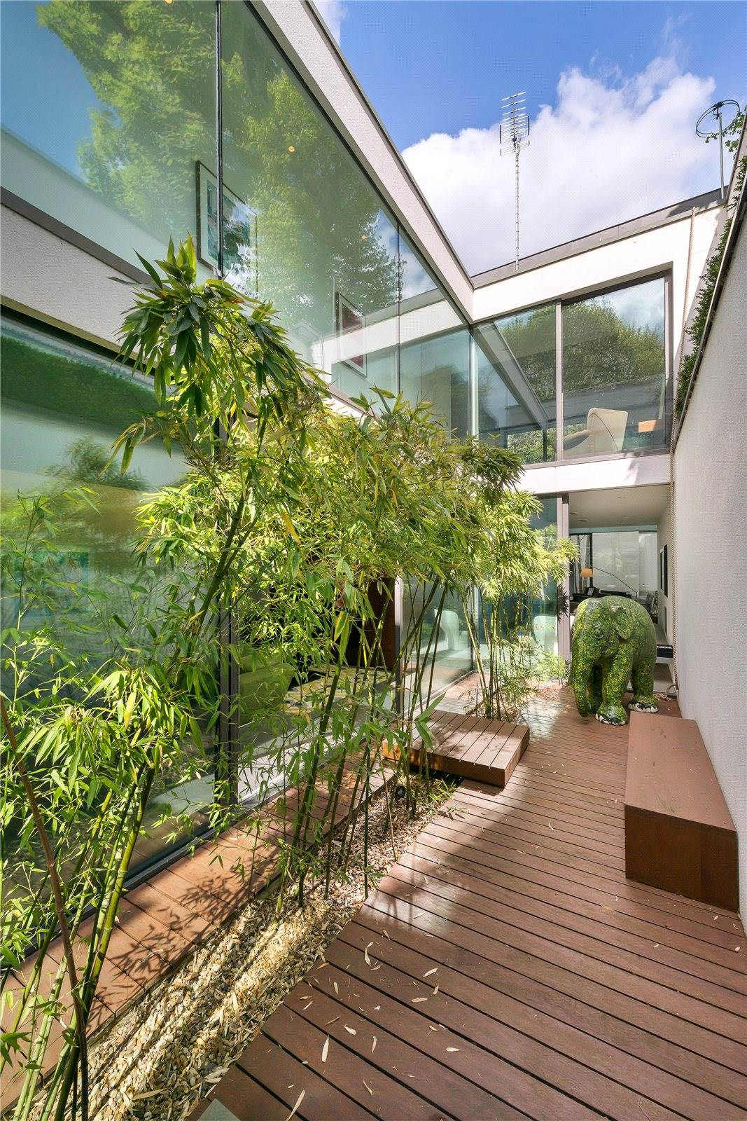 The living quarters are arranged over two stories, designed around a two-story atrium featuring an enchanting Japanese <i>Tsubo niwa</i>-style garden with lush plants and stone sculptures.
