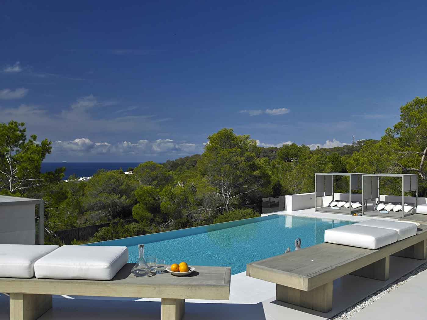 The glamorous island of Ibiza is the setting for this luxury villa. An infinity pool evokes a chic, resort-style atmosphere with daybeds, cabanas, and views of the surrounding greenery and deep sapphire-blue waters.