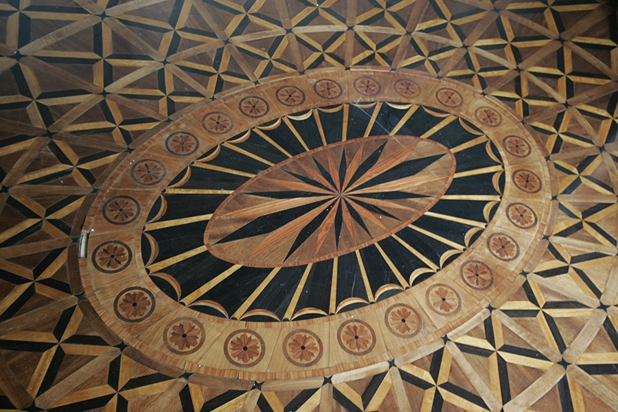 Some of Castle Po's marquetry floors are Neoclassical in style, such as this well-preserved oval form with a starburst pattern at the center.
