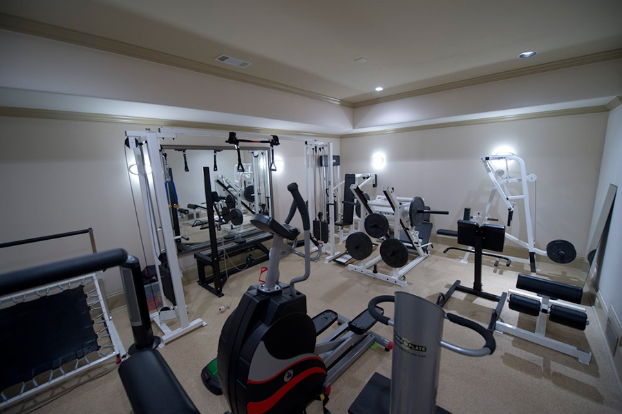 The home gym has recessed lighting and a mirrored wall, plus enough room for a full suite of exercise equipment and free weights.