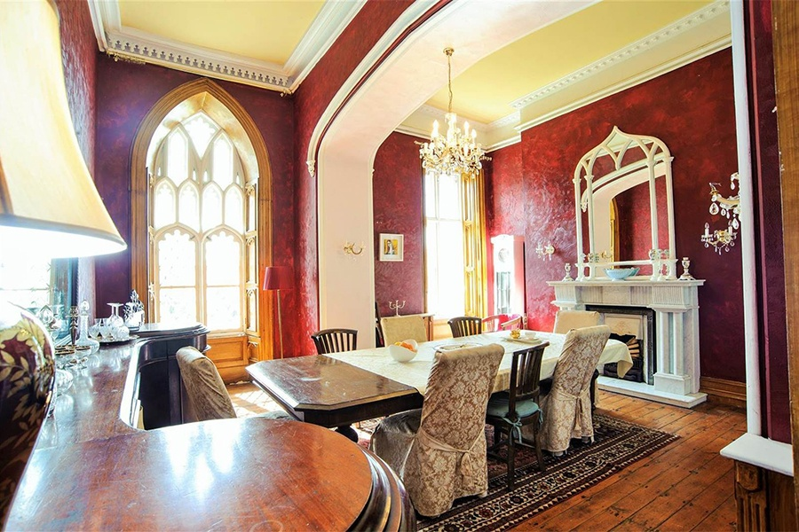 This 1830 estate in County Cork, Ireland, combines the structure of a classic farmhouse with Gothic-style details such as its two grand pointed windows, carved limestone portico, entry hall with a fan-vaulted ceiling, and baronial-style stone fireplace.