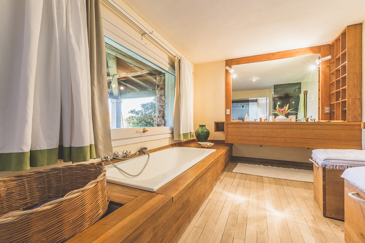 Villa Libeccio's beautiful bathroom follows the same architectural ethos as the rest of the house: all-natural wood and stone finishes at one with the surrounding environment. Above the soaking tub, a huge picture window opens to the courtyard and pool.