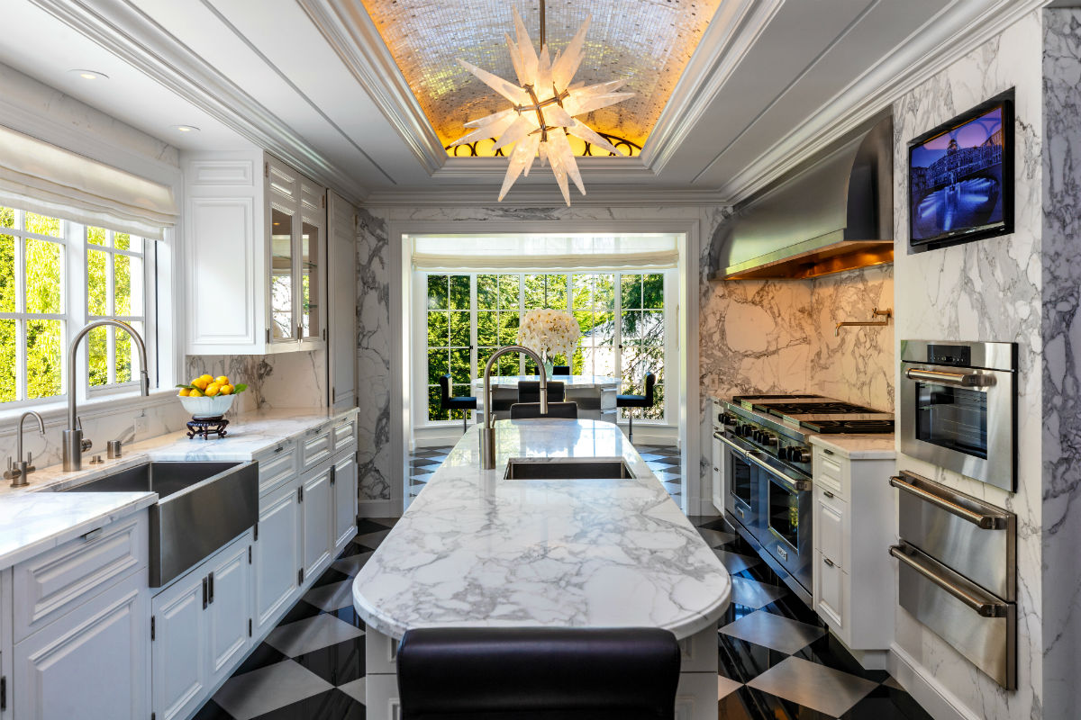 An ultramodern kitchen is appointed with state-of-the-art appliances and gleaming marble surfaces.