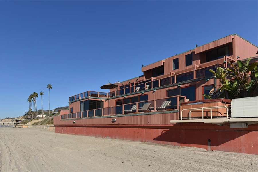 This architectural marvel takes full advantage of its beachfront location with large windows and a private deck for sunbathing and sunset watching.