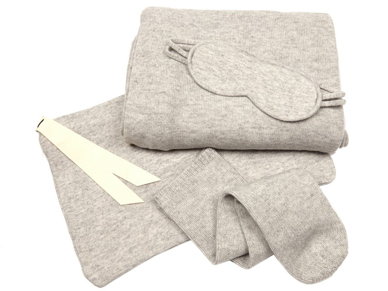 Le Kasha's unisex travel set contains matching socks, eye mask, and large travel blanket with discreet buttons; the bag itself becomes a pillowcase.