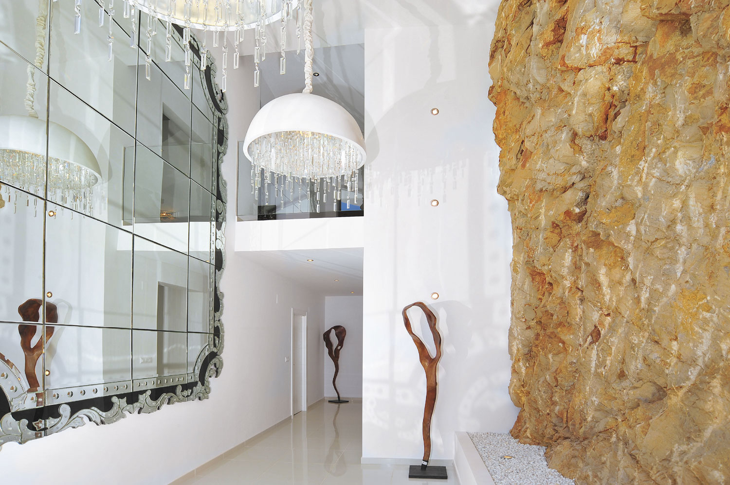 A gallery entrance with sculptural light fixtures, housed in a lighthouse-style rotunda facing the sea, lends to the luster of this Spanish villa on the Costa Blanca.