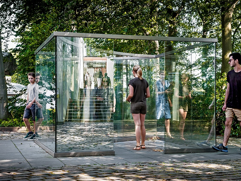 The stainless-steel and two-way-mirror glass piece, <i>Square Bisected by Curve</i> by New York-based artist Dan Graham, is on display at the Louisiana Museum of Modern Art in Denmark. Photograph: Kim Hansen. Credit: Louisiana Museum of Modern Art.