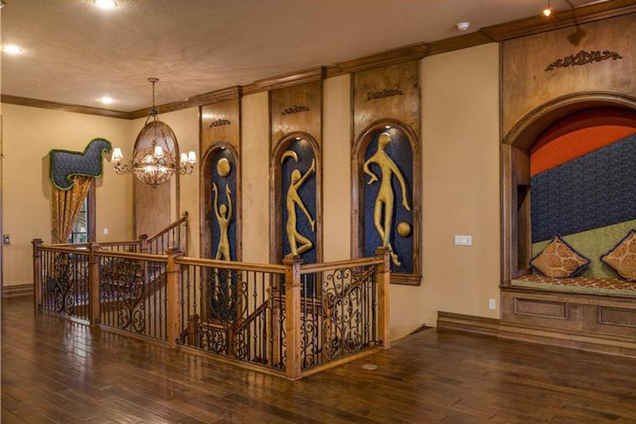 The basketball-themed panels rising alongside this stairwell are a reminder that this opulent lakefront mansion was previously owned by eight-time NBA All Star and 2008 Olympic starting center Dwight Howard.