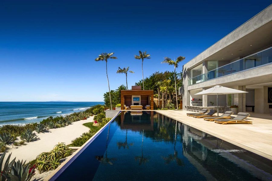 This spectacular seven-bedroom oceanfront estate designed by famed local architect Douglas Burdge sits right on the Pacific Ocean in Malibu—a perfect setting for couples who love sun and sand as much as they love great design.