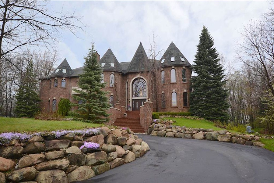 Turrets, arched windows with stone keystones contrasting the exterior red brick, and a grand staircase leading to the double-height entrance give this hilltop home an imposing presence.