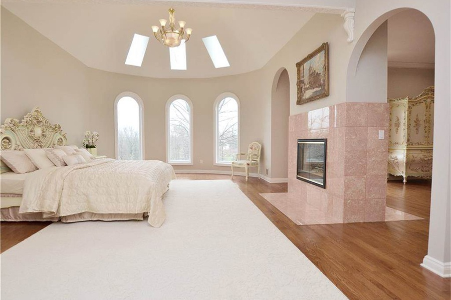 The pink stone fireplace, arched doorways and windows, and circular shape of the master bedroom suite are fit for a princess.