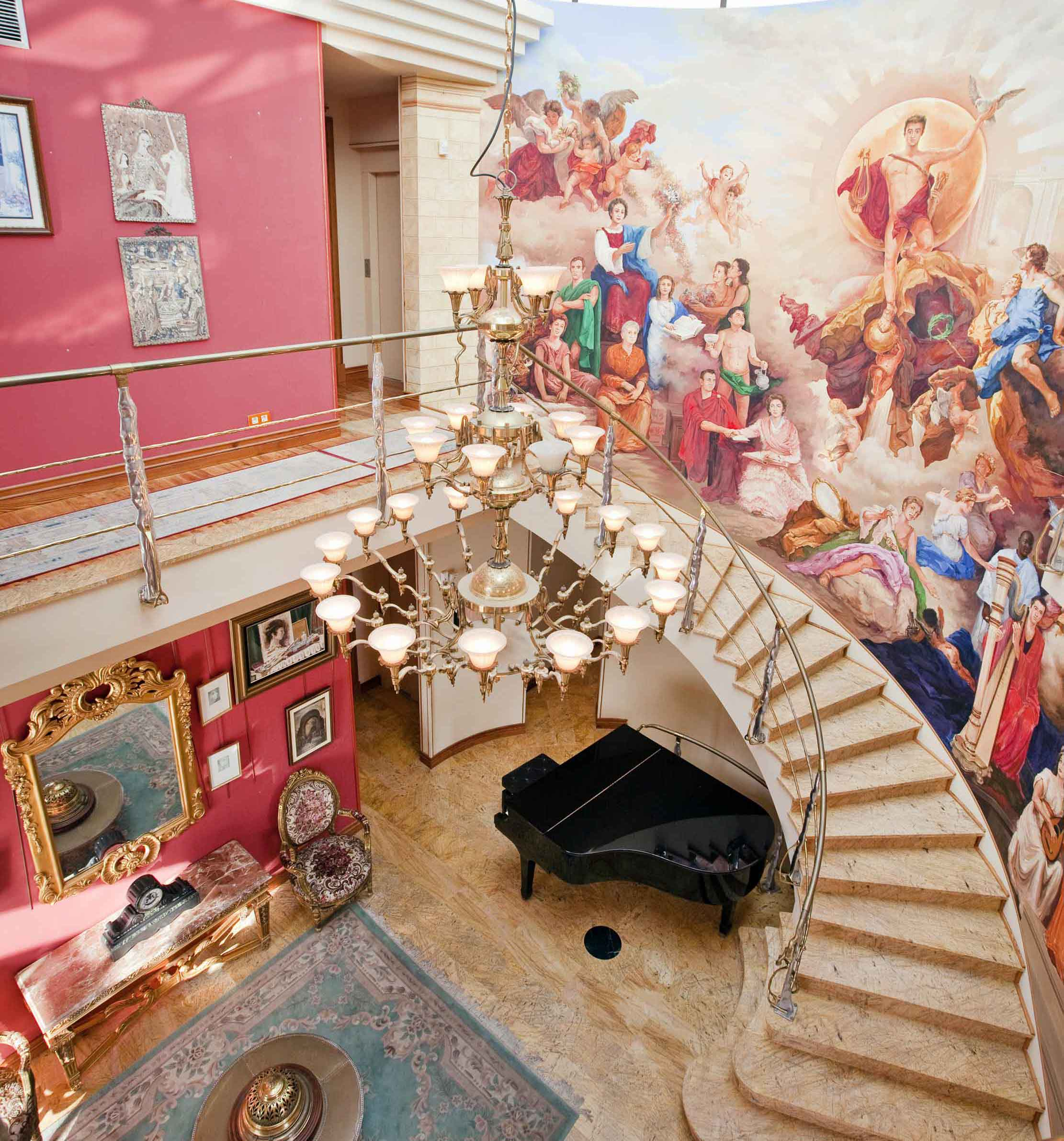 The interior is arrayed with unique artisanal details. The centerpiece of the grand foyer is an extraordinary floating staircase adorned with a mural painted by hand by a local artist and depicting scenes from classical antiquity.