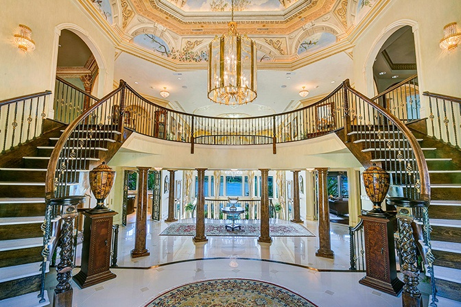 A 2.5-story foyer with a hand-painted ceiling dome and double staircase forms the entrance to this 20,000-square-foot château-style residence on the banks of the Navesink River.