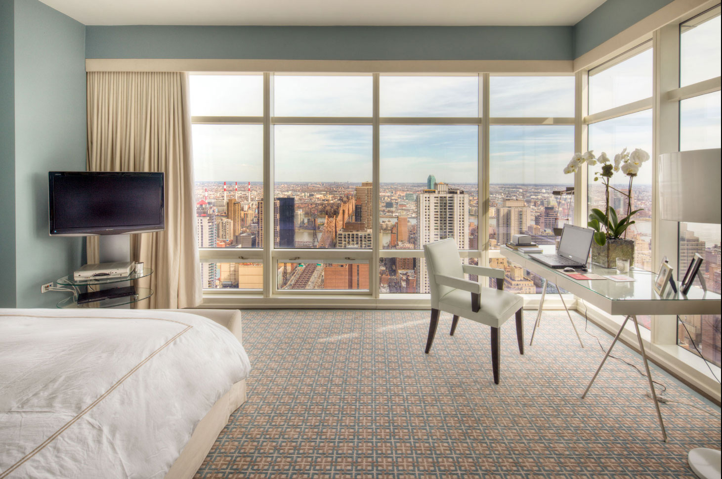 This high-floor contemporary apartment with interiors by Jacques Grange and Richard Mishaan has a lofty location atop atop the headquarters of Bloomberg L.P. in One Beacon Court — one of the tallest buildings in New York City.