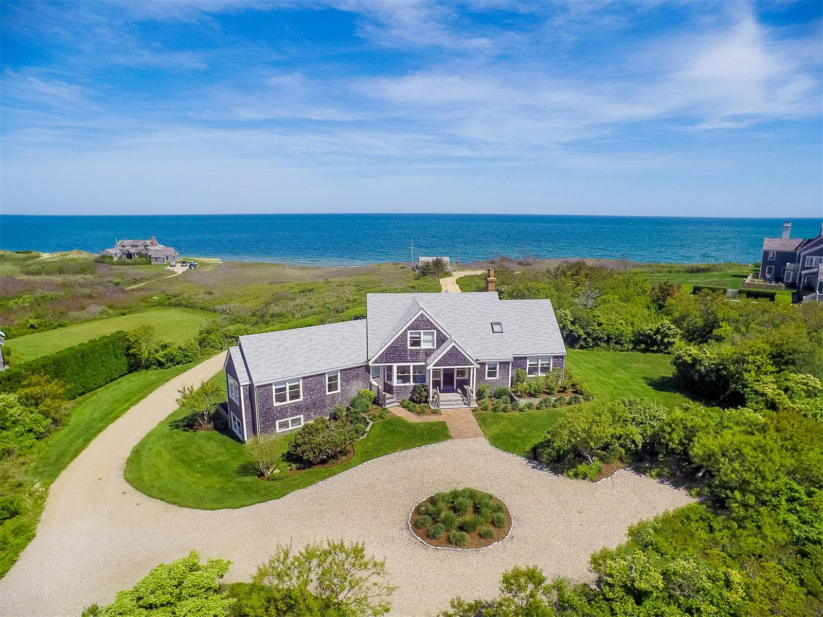 This waterfront estate on Dionis Beach on the island jewel of Nantucket features a charming Shingle-style residence, verdant grounds, and a traditional bath house by the sea.
