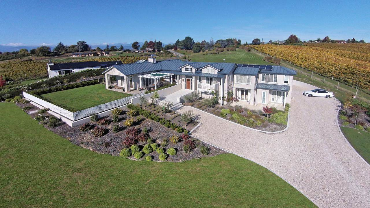 The award-winning design of this New Zealand estate is evident in a view that includes discreetly placed solar paneling and integrated landscaping of vineyards and orchards.