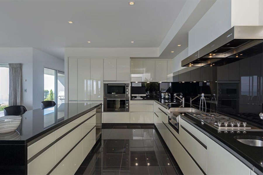 Shiny granite and top-of-the-line appliances compete for attention with the jaw-dropping views from the dazzling kitchen at the heart of this Northern Auckland residence.