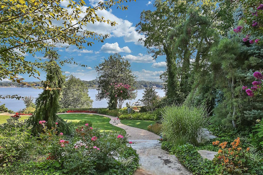 The colorful plantings, grand lawn, and surrounding forests of this New Jersey estate on the Navesink River estuary offer beauty and privacy in a bucolic setting.