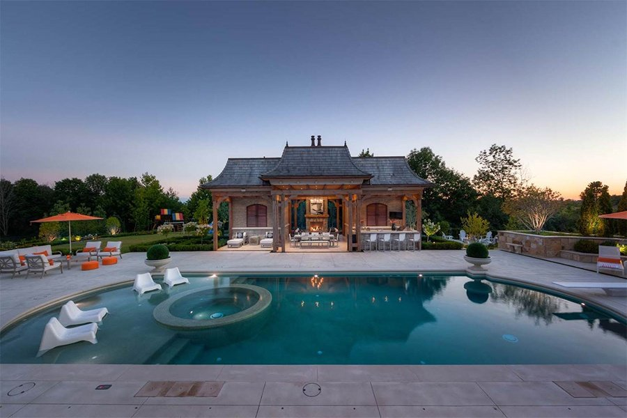 A pool area with in-pool and poolside seating, an outdoor chess board, and a cabana with a bar, fireside seating, dining area, and shaded lounge area make outdoor summer entertaining easy at this Ontario estate.