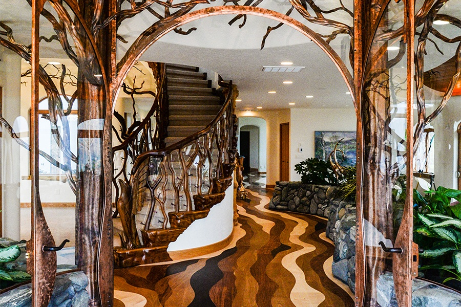 The custom wood flooring and fantastical shapes of the entryway's curving wooden staircase, with its branch banister and carved raven newel posts, invite guests into a fairytale.