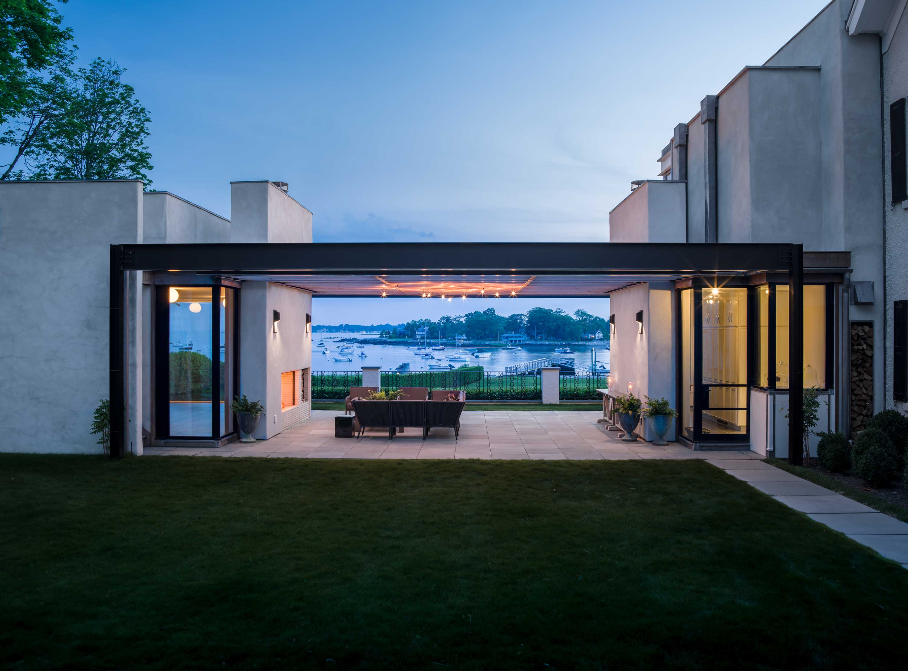 Framed by the picturesque backdrop of Long Island Sound, the outdoor entertaining terrace is a luminous haven with a fireplace and high-tech light installation.