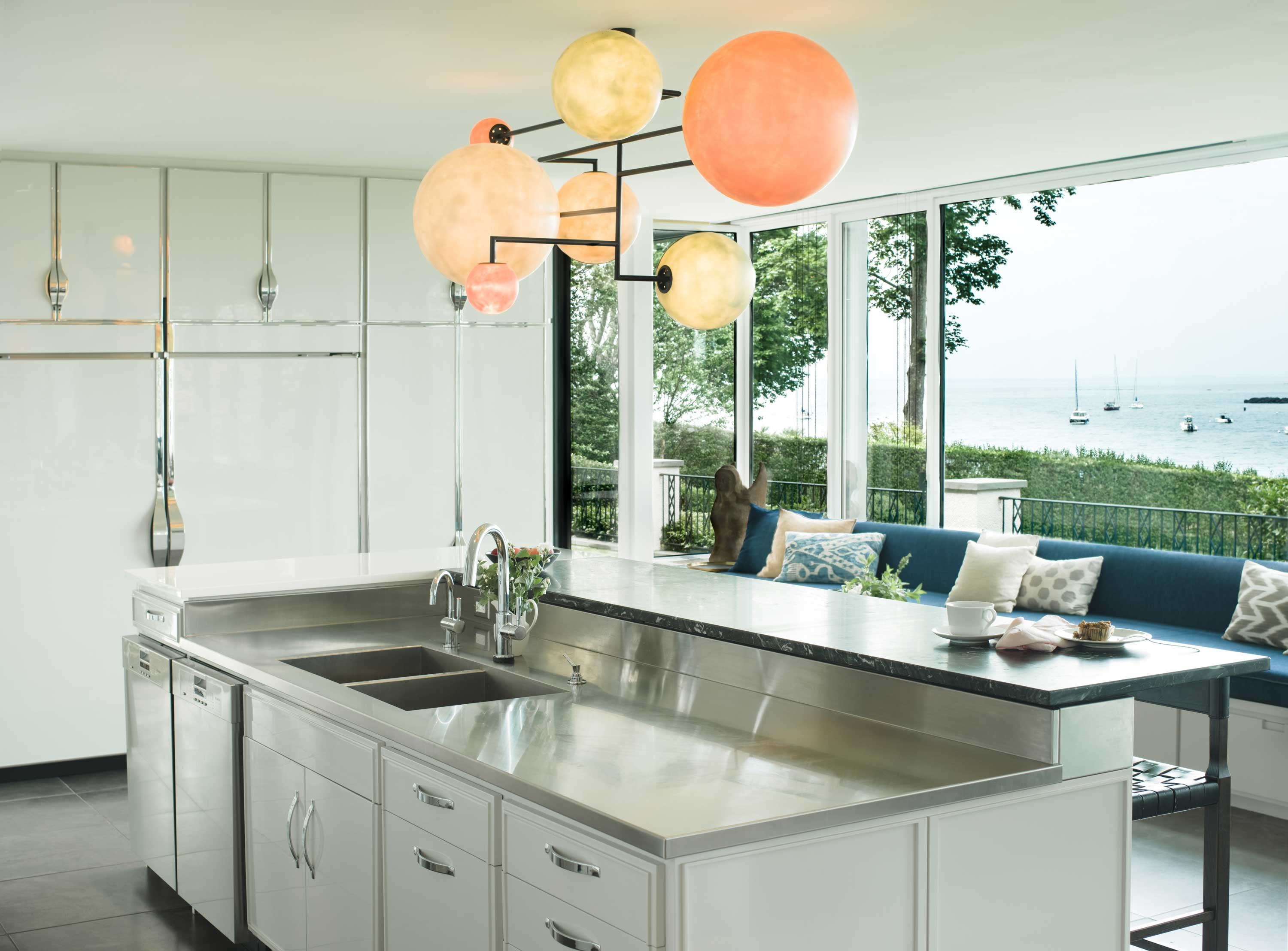 Artisan light fixtures have been beautifully placed throughout the interior; this opalescent multi-light pendant adds a burst of color to the contemporary kitchen.