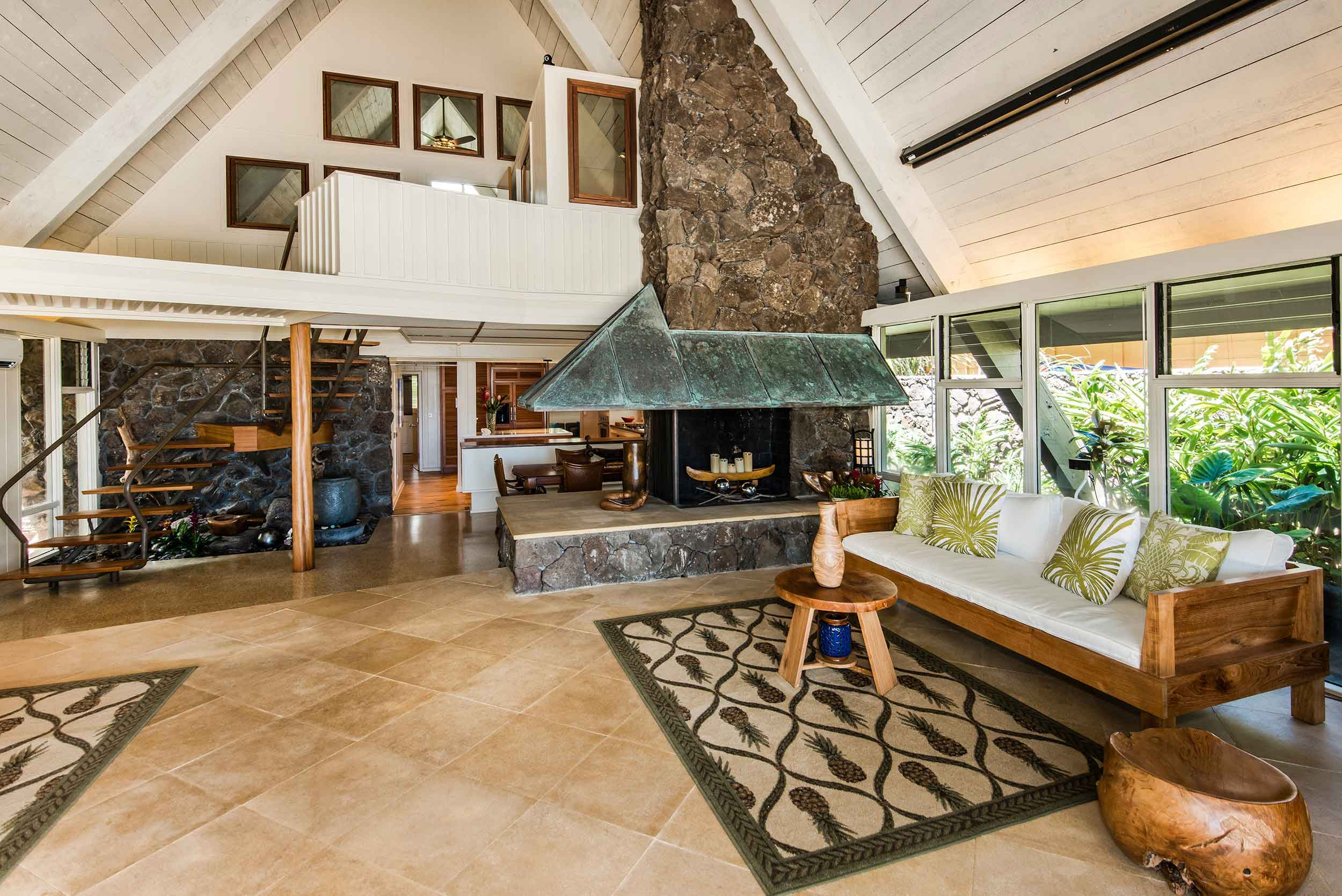 This Mid-century beachfront paradise abounds with locally materials, such as lava rock and hardwood, which have been artistically crafted into the framework of the house.