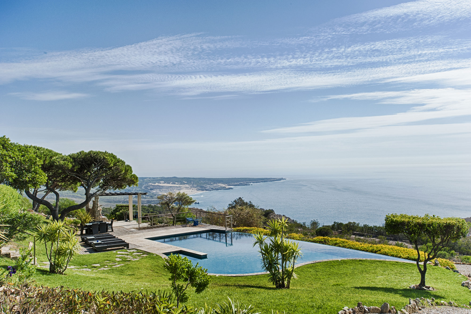 At this contemporary seaside villa, lush gardens and an infinity pool punctuate the sweeping views of Portugal's Sintra coast.
