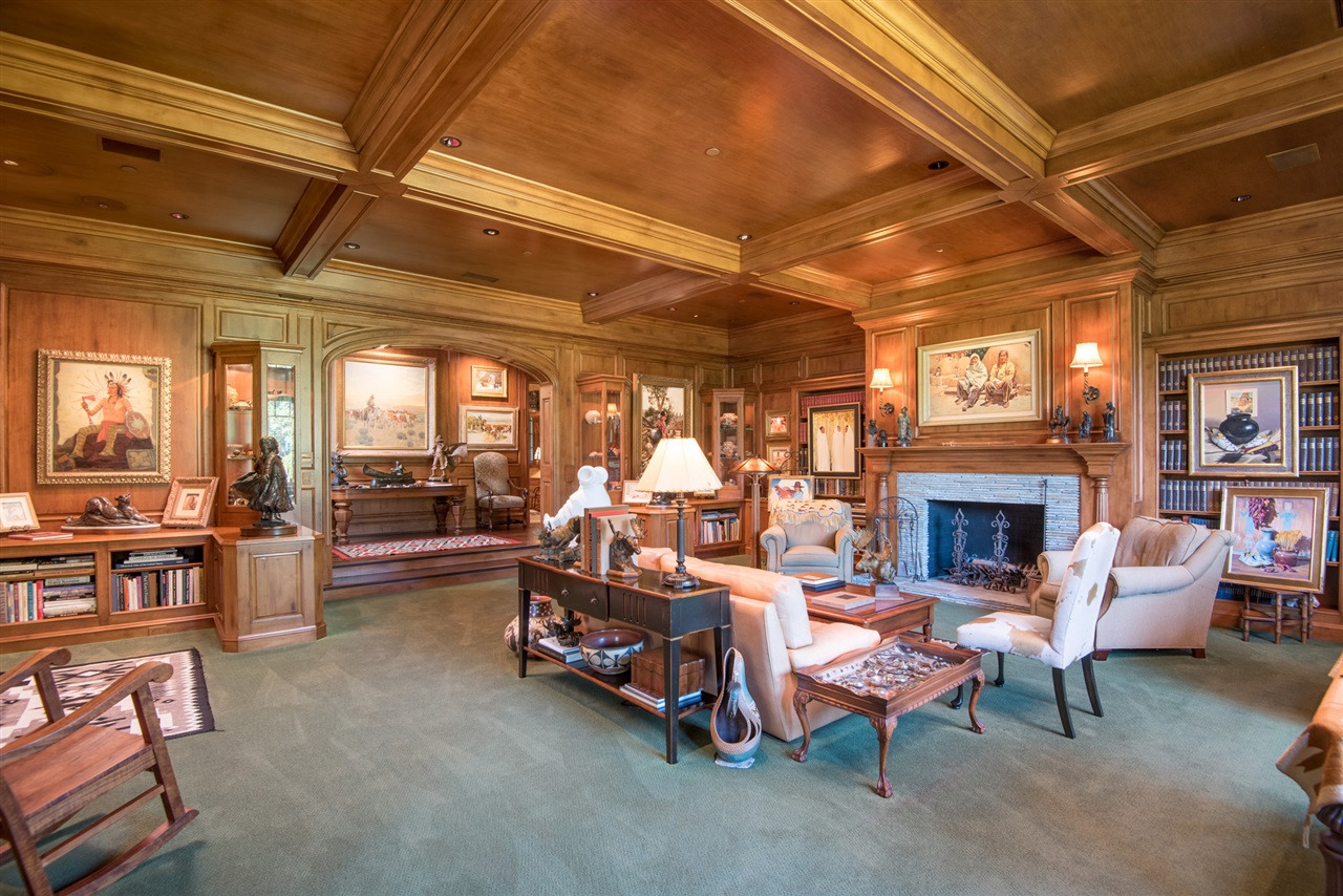 This gated estate in Ranch Santa Fe is a bibliophile's dream with its wood-paneled library warmed by a monumental stone fireplace.
