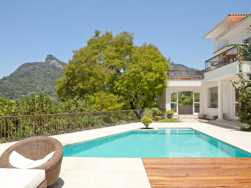 Providing an incredible view of Christ the Redeemer, this impeccable 6,607-square-foot property in Rio de Janeiro's Santa Teresa district boasts five en suite bedrooms, modern living areas, and a dazzling pool terrace and verandah.