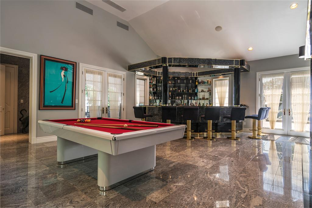 This Colonial-style manor in Saddle River, New Jersey, boasts three wet bars, including an elegant English-style bar with custom-built mahogany finishes and glass bottle display area.