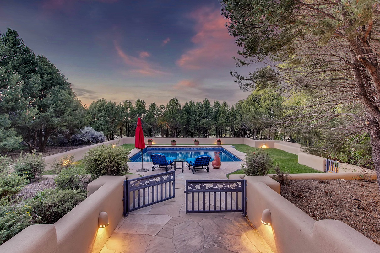 This 35-acre equestrian estate, just 10 minutes from the Santa Fe Plaza, features a traditional double-adobe home with classic details such as kiva fireplaces, viga wood beams, and covered porches.