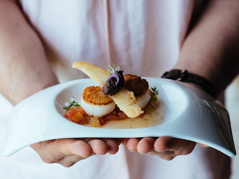 On an island with a centuries-old fishing culture—not to mention a French-trained executive chef—the seafood, such as this exquisite dish of Seared Scallops, is exceptional. Photograph: Saki Papadopoulos