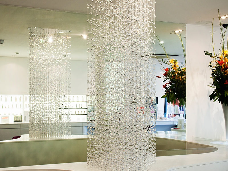 """Inspired by a """"water"""" brief, Crystal Waterfall is a column of 10,000 glass droplets suspended on extra-long wires."""