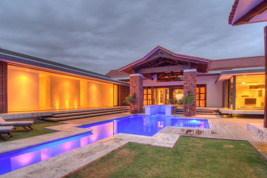 The dramatically lit pool, bar, and dining area of this South African estate promise long, pleasant evenings in a subtropical climate.