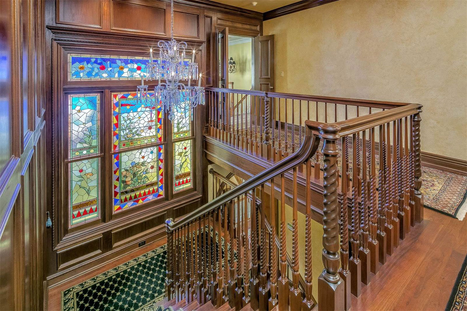 A grand staircase with a 19th-century stained-glass window is one of the many decorative art forms that grace the Victorian-Revival manor house at Hidden Meadow Farm.