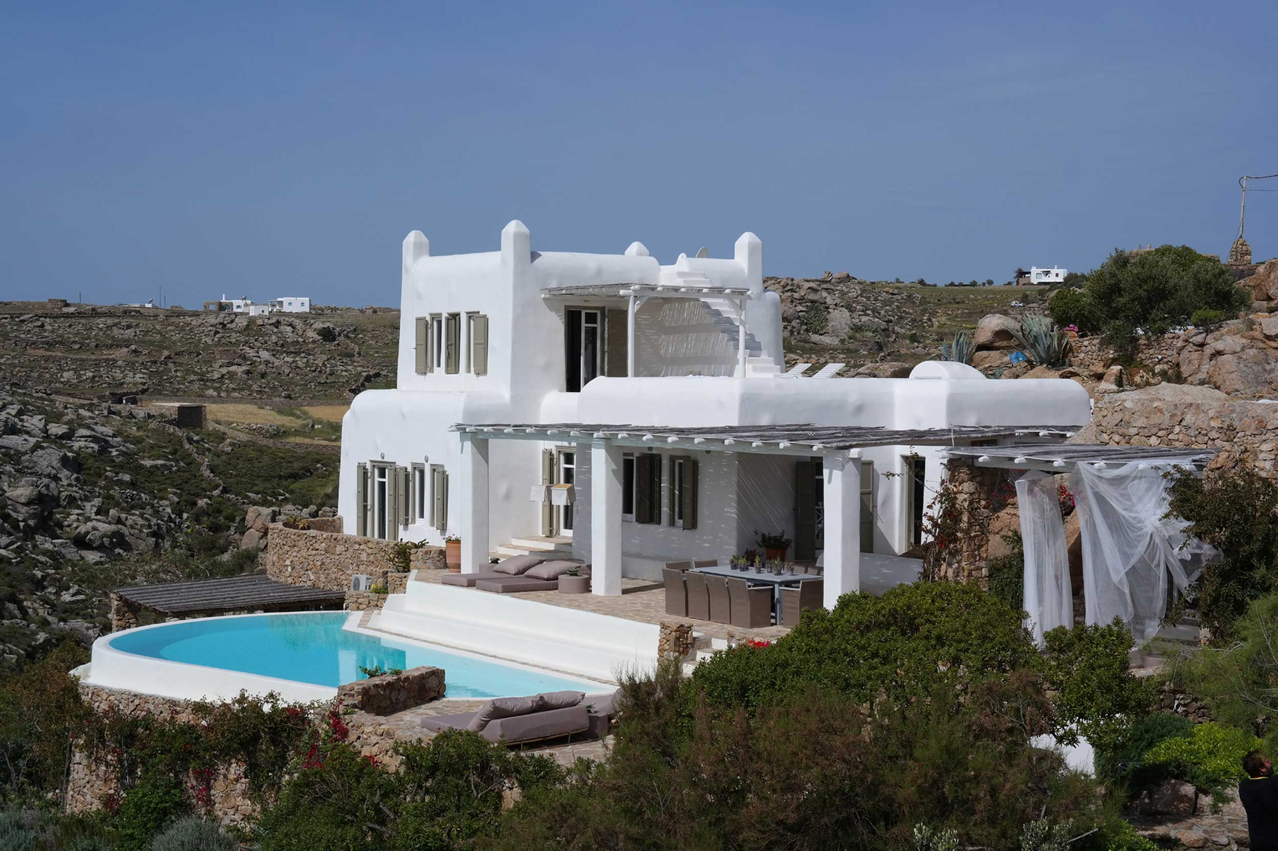 Perched on a hill above the famous southern beach of Agrari, this elegant villa exudes luxury and warmth, and is only a short stroll from white sand and crystal clear waters.