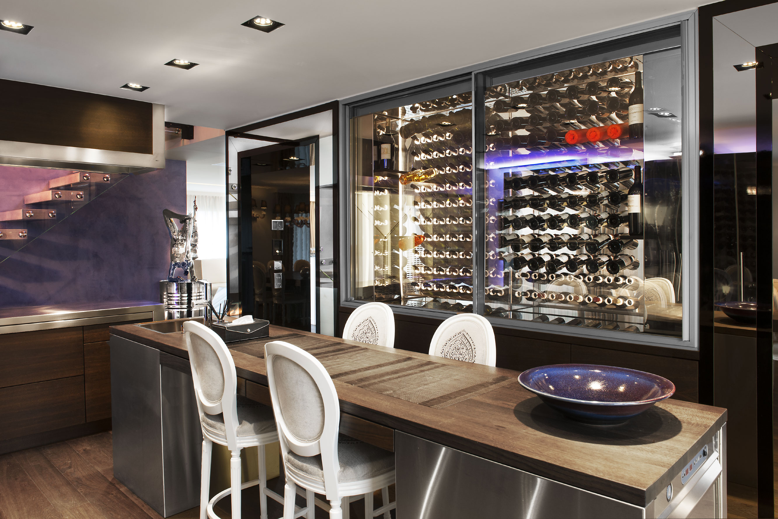 This contemporary apartment in Confignon, a picturesque suburb of Geneva, has a sleek multi-bottle wine display, with temperature-controlled storage, overlooking the dining room.